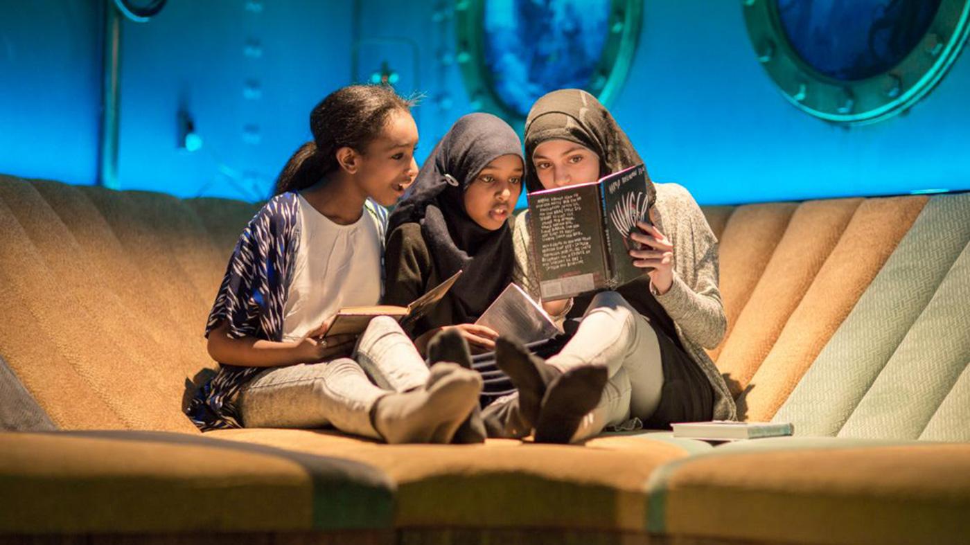 Tre barn sitter og leser bok på Tøyen Deichmanske bibliotek