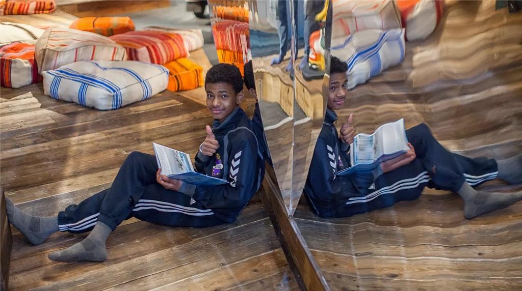 Gutt sitter og leser bok i bibliotek